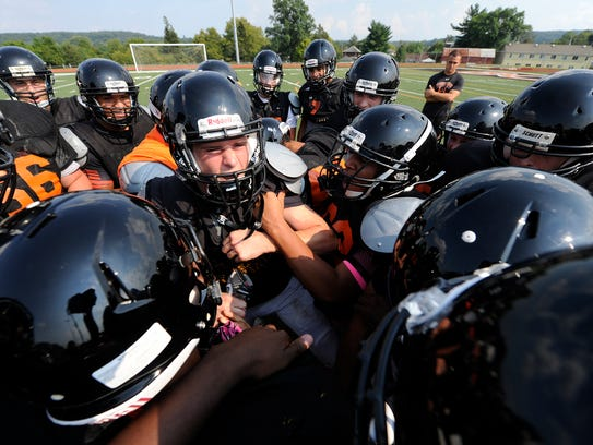 The Northeastern football team huddled up for the first