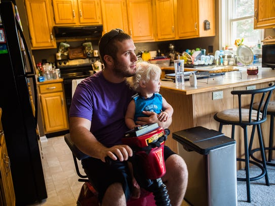Breighton Engelhart holds his 16 month-old son, Daniel,