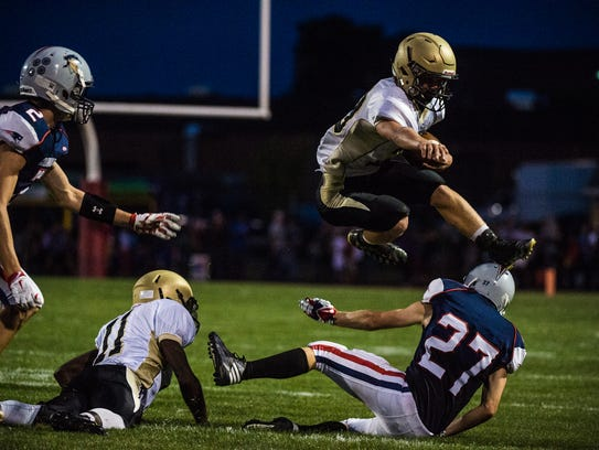 Delone's Ryan Hart leaps over New Oxford's Kyle Lovisone