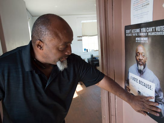 Pastor Kenneth Glascow hangs up signs letting people