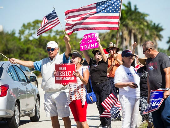People wave signs and flags at traffic in support of