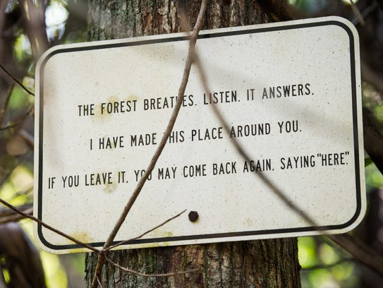 A sign hangs on a pole on the property of the late