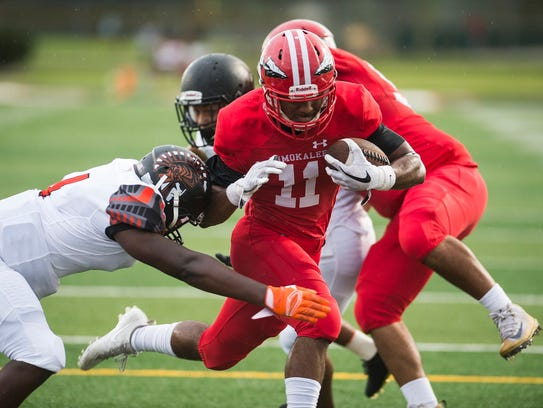 Immokalee High School's Malcom Jackson takes the ball