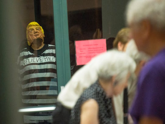 A man dressed as President Donald Trump looks in while people gather for a town hall discussion about immigration law enforcement at the Unitarian Universalist Congregation of Greater Naples church in Golden Gate Estates, Fla., on Tuesday, Dec. 5, 2017.