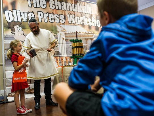 Kids learn how olive oil is handpressed at a workshop