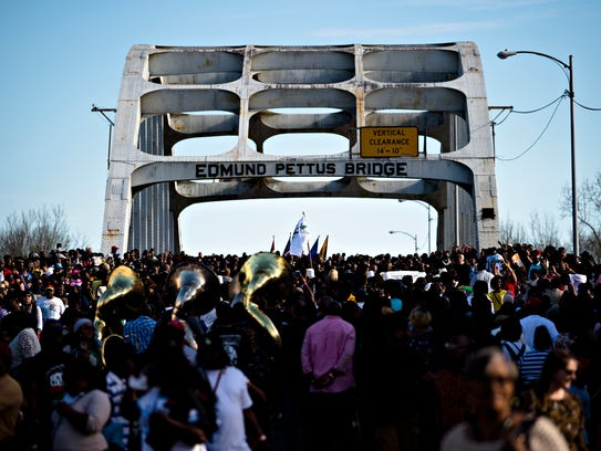 Thousands of people walk across the Edmund Pettus Bridge