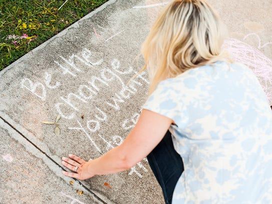 Liz Kellar writes on a sidewalk at the Estero Community
