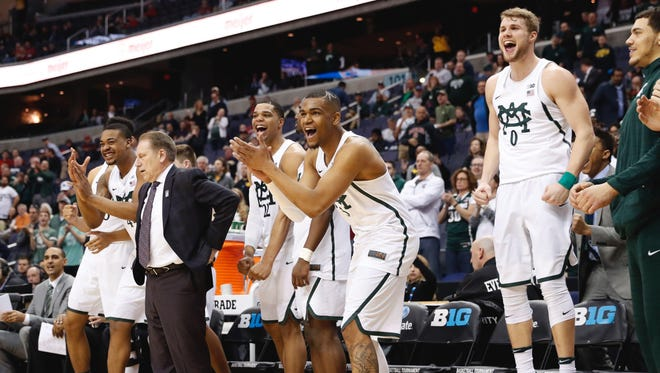 Michigan State players including guards Kyle Ahrens, right, and Alvin Ellis III, second from right, react from the bench late in the second half of MSU's 78-51 win over Penn State in the Big Ten tournament Thursday in Washington.