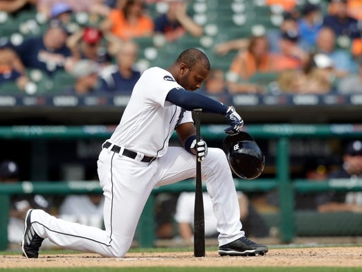 Tigers leftfielder Justin Upton kneels after striking