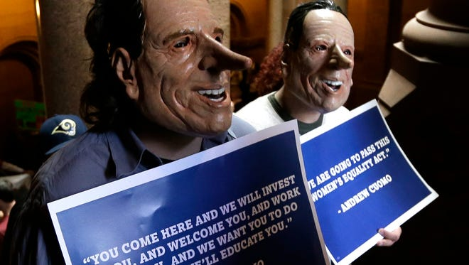 Demonstrators wearing masks resembling Gov. Andrew Cuomo rally against the proposed state budget outside at the Capitol on Monday in Albany. Demonstrators wearing masks resembling  Gov. Andrew Cuomo rally against the proposed state budget outside at the Capitol on Monday, March 31, 2014, in Albany, N.Y. The state Legislature began debating a $140 billion budget due by the beginning of the fiscal year at midnight. (AP Photo/Mike Groll)