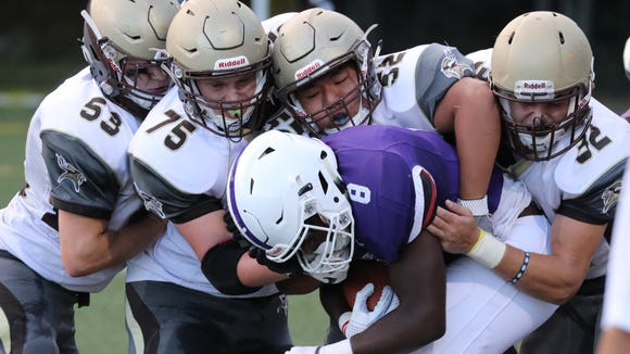 New Rochelle ball carrier Jordan Forrest is brought down by South defenders including from left, TJ Grogan, Daniel Smith, Arnett Jung and Sam Franco during the New Rochelle vs. Clarkstown South football game at Fosina Field in Flowers Park in New Rochelle, Sept. 8, 2017