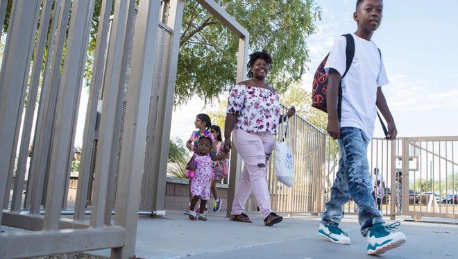 Lancer Williams, 9, Tinisha Loring and Talayah Williams, 1, walk through the gates of Kyrene de las Lomas Elementary School on Thursday, August 3, 2017 in Phoenix, Ariz.
