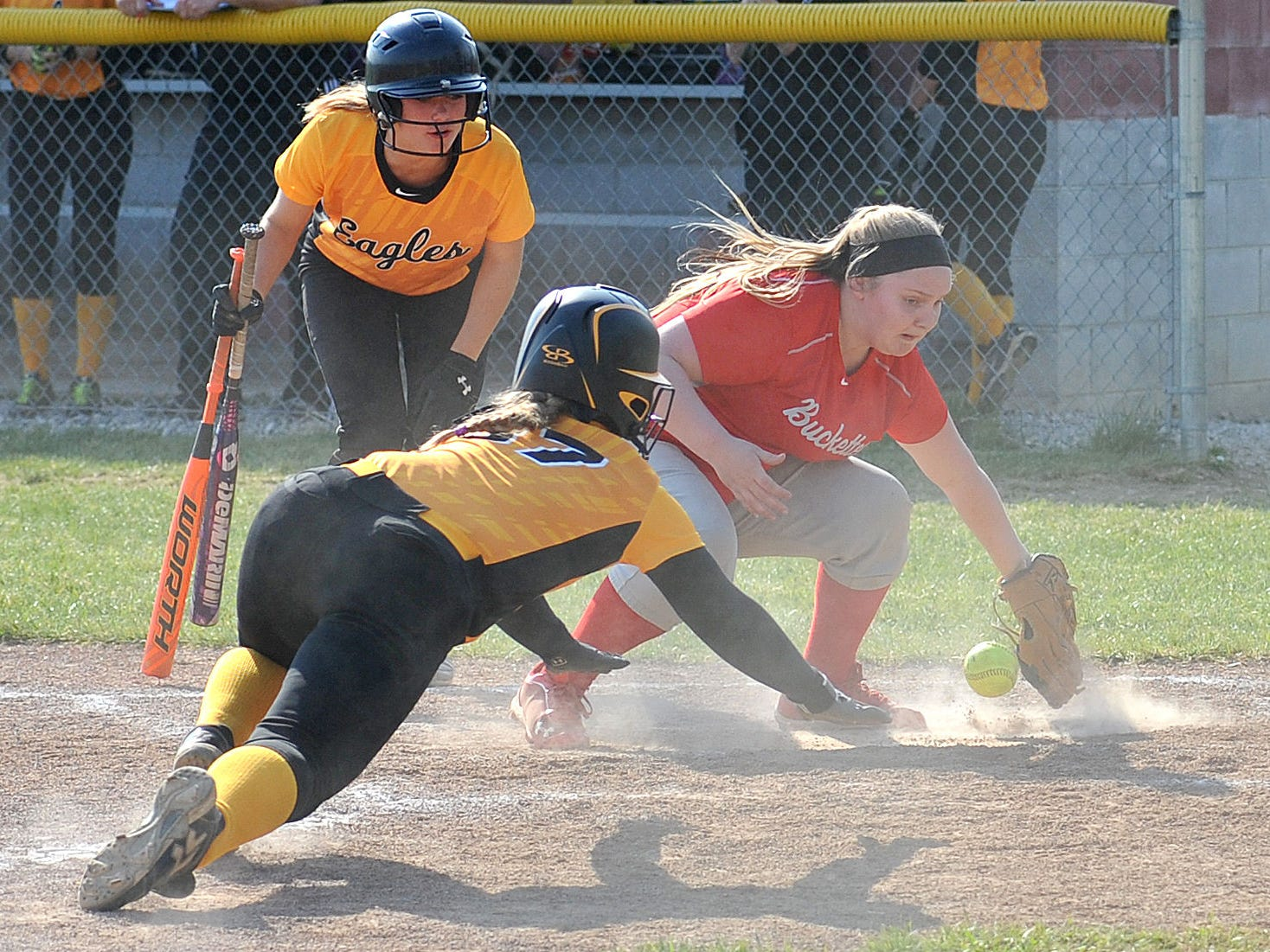 Colonel Crawford's Lexi Hoepf slides safely to home plate as Buckeye Central's pitcher, Tiffany Armstrong, fumbles with the ball during their game Wednesday evening.