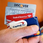 Steve Wheelock holds up his Discover Card along with his American Express, Bank of America and Capital One Visa credit cards in San Francisco.