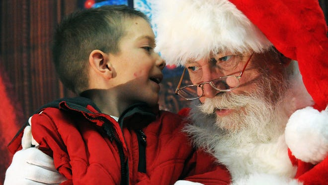 Dillon Cringle of Las Cruces whispers his name into Santa's ear at 2014 Downtown Main Street celebration. Weekend events will also include an open house at White Sands National Monument and Noche de Luminarias on the NMSU campus.