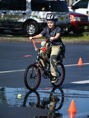 Charles Mitchell navigates the bike track during the free Safety Fair and Bike Rodeo on Saturday, May 6, at Corkscrew Middle School.