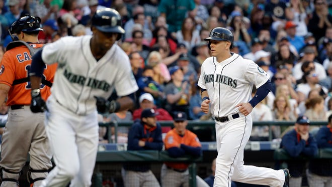 Seattle Mariners' Logan Morrison, right, walks in to score and Austin Jackson heads to first on a bases-loaded walk as Houston Astros catcher Jason Castro turns away from the plate during the second inning of a baseball game Saturday, June 20, 2015, in Seattle.