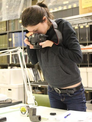 MTSU public history graduate student Dakota Elliott photographs potential artifacts at the McClung Museum of Natural History and Culture for potential use at the Old Stone Fort State Archaeological Park Museum in Manchester.