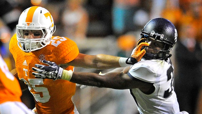 Tennessee wide receiver Josh Smith (25) stiff arms Utah State safety Devin Centers (37) as the University of Tennessee plays Utah State at Neyland Stadium.  Sunday Aug. 31, 2014, in Knoxville, TN.
