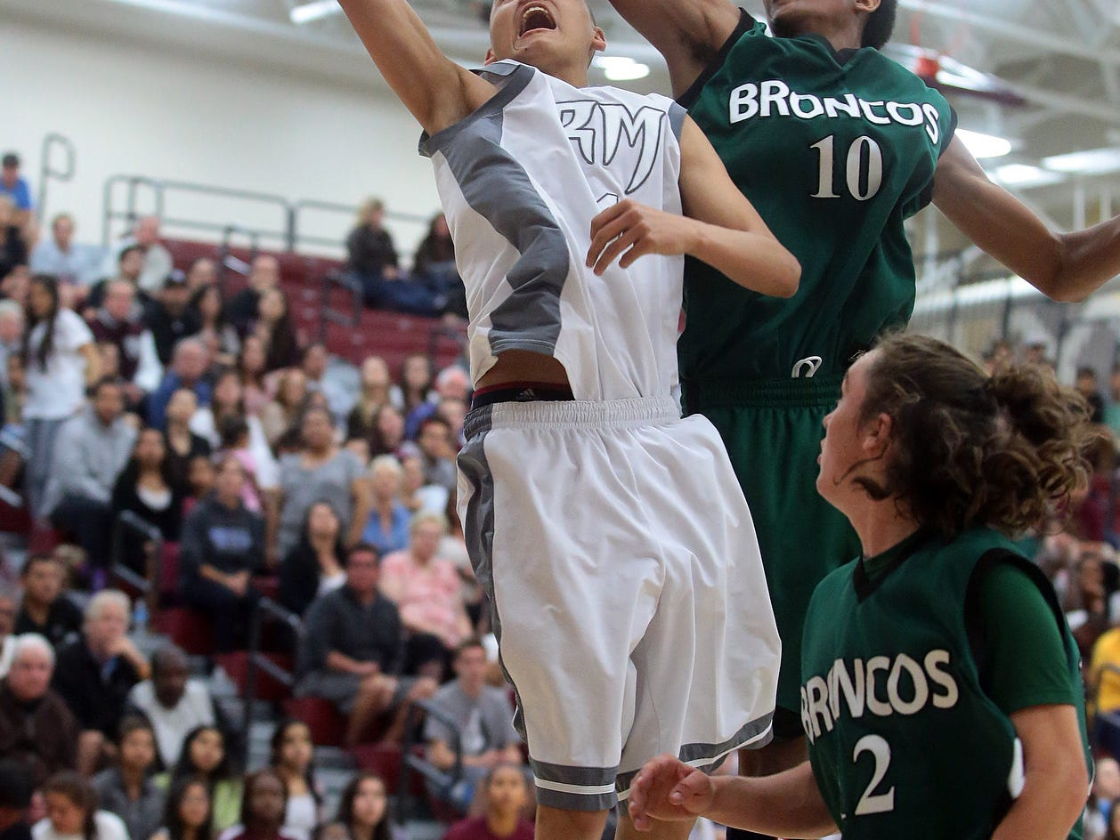 Charles Neal of Rancho Mirage (4, white) has a shot blocked by Banning's Quincy Boxley (10, green) on Wednesday, February 18, 2015 during a first-round CIF playoff game. Neal scored 17 points and finished as the leading scorer for Rancho Mirage in their 81-56 victory.