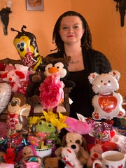 Nichole Weaver, owner of N&J's Sweets and Treats, poses with some of the items she offers in her gift baskets on Thursday at her home in Bloomfield.