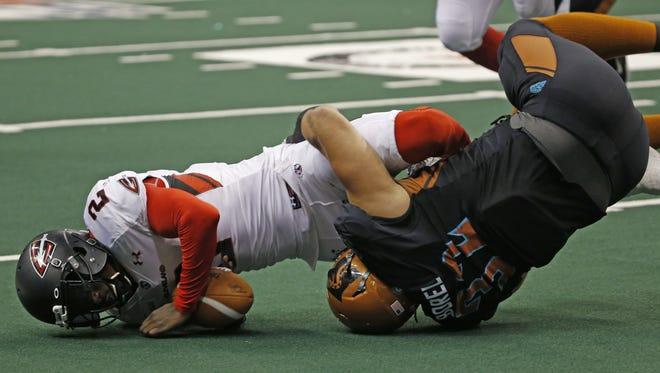 Rattlers' Damien Borel (32) sacks Gladiators' quarterback Arvell Nelson (2) at Talking Stick Resort Arena on July 24, 2016 in Phoenix, Ariz.