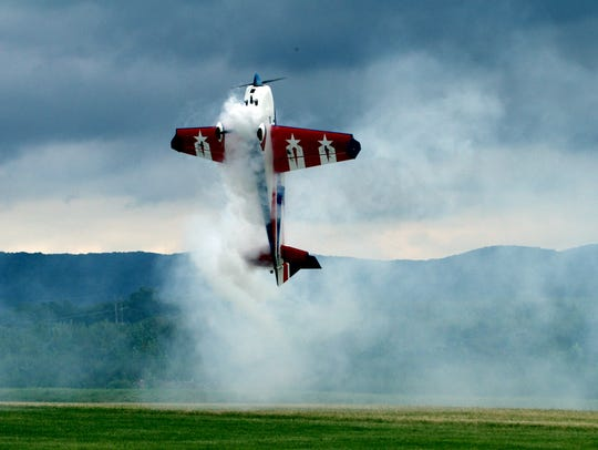 A model plane billows smoke as it hovers before ascending