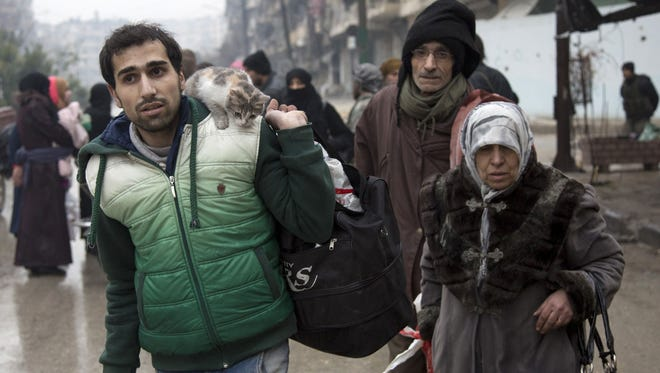 Syrians leave a rebel-held area of Aleppo towards the government-held side on Dec. 13, 2016 during an operation by Syrian government forces to retake the embattled city.