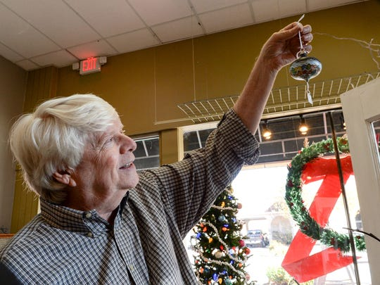 Mike Pruitt of Gallery 313 holds a hand painted Christmas ornament on Monday. Pruitt and coworkers get ready for their Friday, November 17 evening Holiday Open House in downtown Anderson.