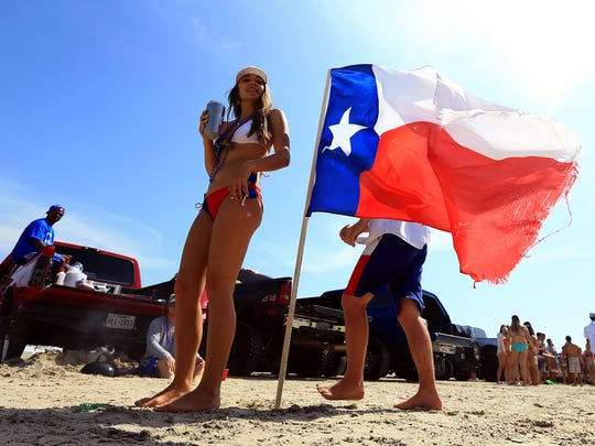 Port Aransas beach goers stand near a Texas flag planted in the sand during spring break 2016.