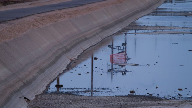 An upside-down grocery cart makes its home in the low, still water of the Grand Canal in Phoenix.