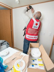 Red Cross volunteer Manny Sanchez installs a new smoke