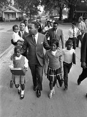 Dr. Martin Luther King Jr. walks between seven-year-old