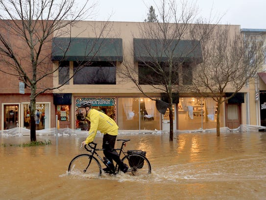A man cycles through floodwaters in downtown Healdsburg,