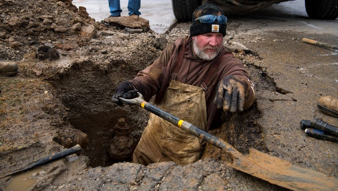 Kevin Capps with the Henderson Water Utility swaps his shovel for a ratchet to complete the installation of a repair band on a broken 6-inch water main on Drury Lane Tuesday afternoon. The utility has been kept busy with a multitude of main breaks this season.