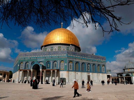 Palestinian Muslim worshippers walk past the Dome of