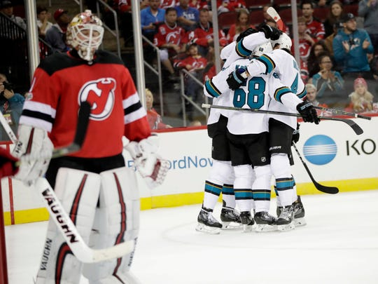 San Jose Sharks players, right, celebrate a goal by Melker Karlsson (68), of Sweden, as New Jersey Devils goalie Keith Kinkaid, left, skates away during the first period of an NHL hockey game, Friday, Oct. 20, 2017, in Newark, N.J.