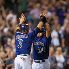 DENVER, CO - JUNE 4: Michael Cuddyer #3 and Wilin Rosario #20 of the Colorado Rockies celebrate the go-ahead run against the Arizona Diamondbacks in the seventh inning at Coors Field on June 4, 2014 in Denver, Colorado. The Doamondbacks beat the Rockies 16-8. (Photo by Dustin Bradford/Getty Images)