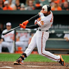 Aug 3, 2014; Baltimore, MD, USA; Baltimore Orioles right fielder Nick Markakis (21) hits a solo home run in the first inning against the Seattle Mariners at Oriole Park at Camden Yards. Mandatory Credit: Joy R. Absalon-USA TODAY Sports