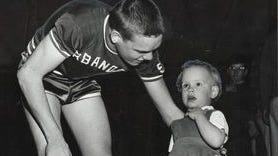 Urbandale's Ron Johnson talks to young cheerleader Debra DeWitt before a January 1959 high school boys' basketball game.