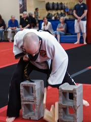 Ed Ogle breaks a block of wood during his fifth-degree black belt test last Saturday at Global Martial Arts Academy in Hampstead, Md.