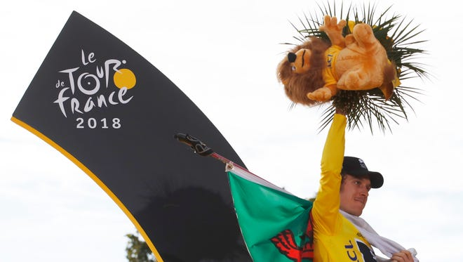 Tour de France winner Geraint Thomas, wearing the overall leader's yellow jersey, celebrates with the flag of Wales on the podium after the 21st stage on Sunday.