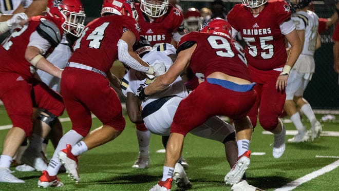 Savannah Christian linebacker Peyton Cromwell (14) and defensive lineman Caleb Womble (99) stop John Milledge's Kelvin Jackson at the line of scrimmage on Friday night at Pooler Stadium. John Milledge Academy won 52-13.SCPS visits Deerfield Windsor this Friday.