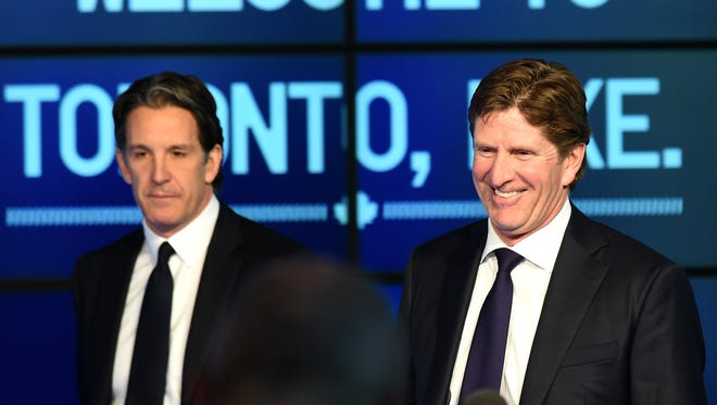 Toronto Maple Leafs coach Mike Babcock, right, smiles as he arrives at an introductory media conference with club president Brendan Shanahan at Air Canada Centre.