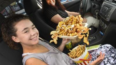 """Shylynn Dunn-Miles, 11, of Monroe was all smiles while she holds butterfly chips, french fries and lemonade as she and her mother, April Dunn, went to seven of the nine food trucks at the first-ever Fair Food Drive-Thru at the Monroe County Fairgrounds this weekend. """"We spent at least one hundred dollars,"""" said April Dunn as they had a picnic out at the fairgrounds."""