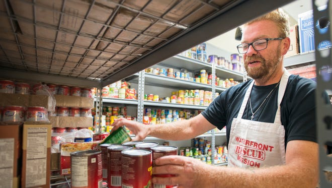 Oliver Mosier, a participant in the career development program, straightens cans in the pantry at the Waterfront Rescue Mission in Pensacola on Monday, June 12, 2017. The organization keeps a well stocked pantry in the event of natural disasters such as hurricanes.