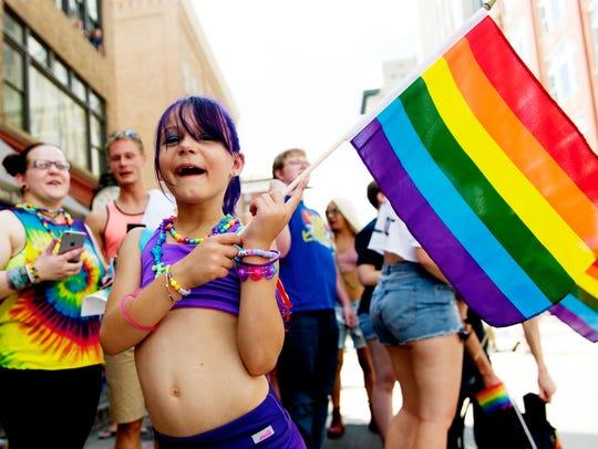 Halliyah Vyrostek, 8, of Knoxville, waves a rainbow
