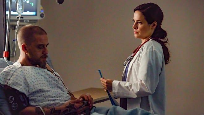 Dr. Mary Harris (Caroline Dhavernas), right, treats a hospital patient (Joel Thomas Hynes) in Lifetime's new drama, 'Mary Kills People.'