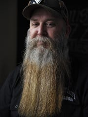 In this Feb. 17, 2019 photo, James Roth poses for a portrait during the first Old Dog Whisker Club meeting of the year at Old Dog Tavern in Kalamazoo, Mich. The Old Dog Whisker Club is a group of men who grow their beards and mustaches for national competitions,(Emil Lippe/Kalamazoo Gazette via AP)