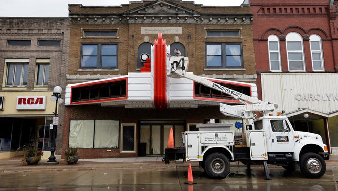 Work is done on the marquis of the Webster Theater, Thursday, Aug. 21, 2014, in Webster City, Iowa.  When the historic downtown movie theater in Webster City, Iowa, went bankrupt and shut down last year, some wondered whether it was further proof of the small town?s demise after a factory closure put hundreds out of work. Instead, residents rallied. They held public meetings, hashed out volunteer work and launched a fundraising campaign. More than $200,000 later, the theater reopened.